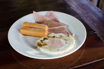 American Breakfast Ham, sausage and Fried egg on the wood table.