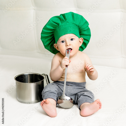 Little boy with metal ladle and cook hat