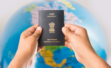 closeup picture of indian man holding indian passport over white background, selective focus