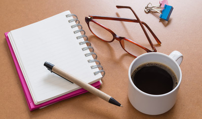 blank open notebook on a brown table with a cup of coffee and eye glasses