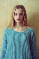 Pretty young girl with blond hair in fashionable sweater