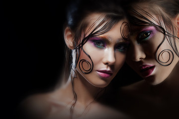 Mysterious portrait with reflection. Alter-ego. Girl with bright makeup and wet hair. Black background