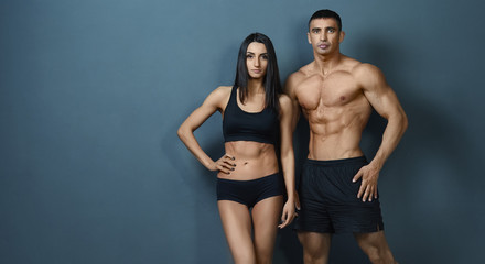 Young couple with a sports body posing against the wall background