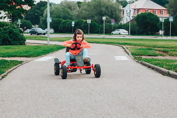 Little girl is riding on pedal karting.