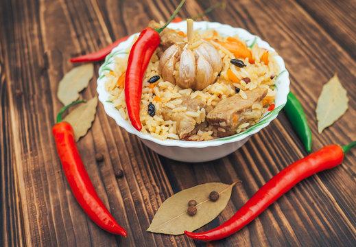 Delicious Fergana pilaf. Uzbek favorite dish on wooden background
