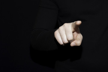 pointing finger on dark background