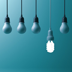 One hanging energy saving light bulb glowing different stand out from unlit incandescent bulbs with reflection on dark cyan background , leadership and different creative idea concept. 3D rendering.