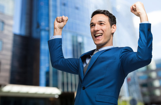 Handsome businessman raising arms in sign of victory