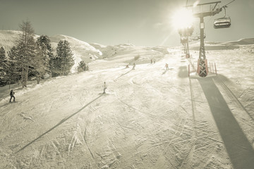 Skiers and snowboarders on the slope at sunny winter day. Desaturated colors