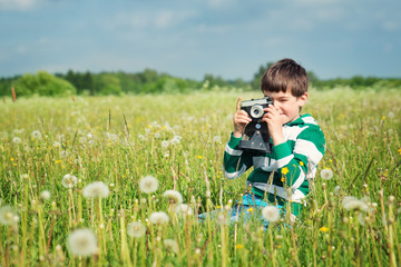 Child wathing in camera on the field with dandelions. Boy playing on the meadow in summer
