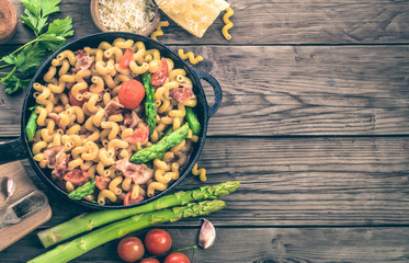 Italian cavatappi pasta with asparagus and tomatoes in frying pan on wooden table, top view with copy space. Toned
