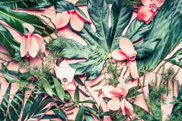 Creative layout made of tropical flowers and palm leaves on pastel pink background, top view,  flat lay Wall mural