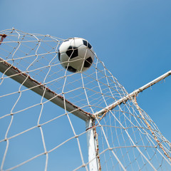 Fototapeta soccer ball in goal. isolated on blue sky background.