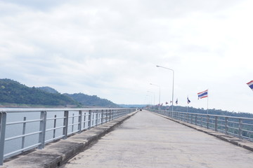 Cement road above the dam with Thai flags.