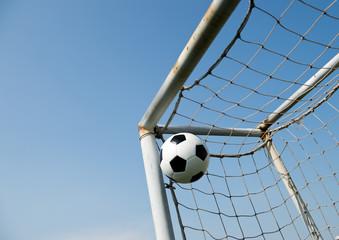 Fototapeta soccer ball in goal on the blue sky background.