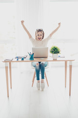 Happy excited successful businesswoman triumphing sitting in the workplace