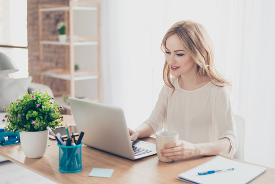 Happy pretty cute woman working with computer drinking coffee