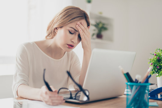 Overworked businesswoman suffering from headache and thinking how to end work