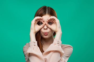binoculars from hands, happy woman on a green background