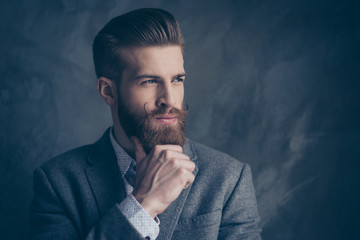 portrait of handsome stylish young man with mustache, beard and beautiful hairstyle keep calm and think while hold beard and chin with hands