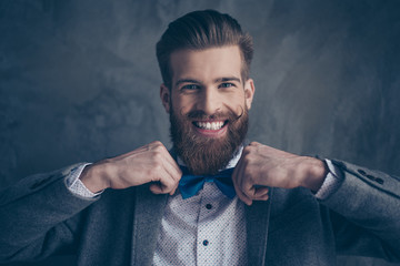 portrait of stylish hipster young man with mustache, beard and beautiful hairstyle make preparation for event party and holding blue bow-tie with toothy smile