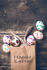 Easter bunny in a paper bag on old boards. Rabbit. Old board background. Easter ideas. Easter eggs. Space for text. Image in trendy toning. On the package text Happy Easter