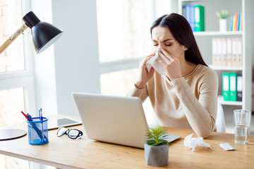 Ill woman sitting at the table with computer at work and using napkin