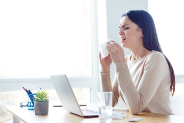 work with deadline. Young ill businesswoman must work on project, sitting at the table with laptop while sneeze at workplace in modern office
