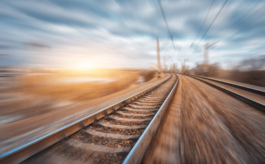 Railroad in motion at sunset. Railway station with motion blur effect and colorful sky with clouds. Industrial concept background. Railroad travel, railway tourism. Blurred railway. Transportation