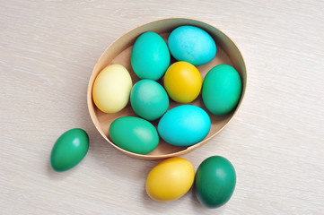 colorful eggs as symbol of Easter in box on wooden background