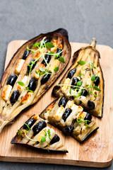 Eggplant  stuffed with black olives and feta on black stone background