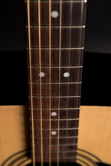 Part of a wooden acoustic guitar on a black isolated background. Vertical frame