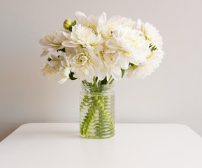 White dahlias in glass jar on white table against neutral background