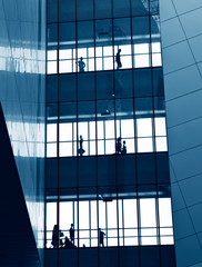silhouettes of business people rushing at morden office building.