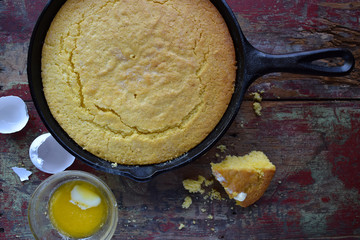 Yellow Cornbread in cast iron skillet on rustic wood table