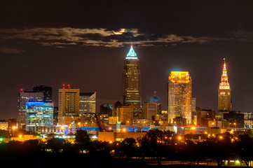 Rising full moon above Cleveland Ohio shining through clouds