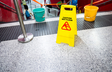 Wet floor caution sign near the stairs.