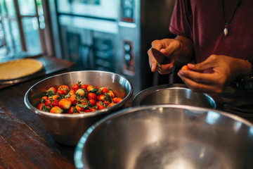 Close up of man hands cutting the strawberries, preparation for cooking dessert