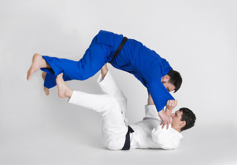 Young sporty men practicing martial arts on light background