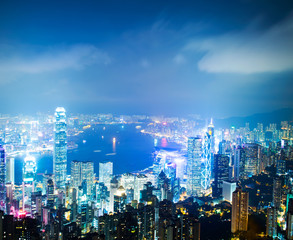 Hong Kong cityscape at night with victoria harbour and large group of tall buildings.