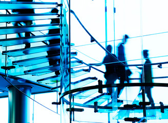 Silhouette people on glass staircase.