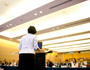 Business woman is making a speech in front of a big audience at a conference hall..