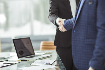 success concept in business - handshake of business partners on the background of the workplace