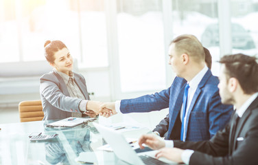 concept of partnership:a handshake of a Manager and a customer at the Desk in the office.