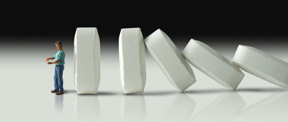 Impending doom and demise of man with pharmaceutical pain medication addiction represented by huge row of pills crashing over like dominoes to eventually crush the man.
