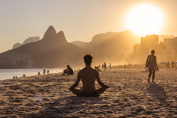 Man on yoga pose during a sunset on Ipanema beach with Morro Dois Irmãos on the background, Rio de Janeiro, Brazil