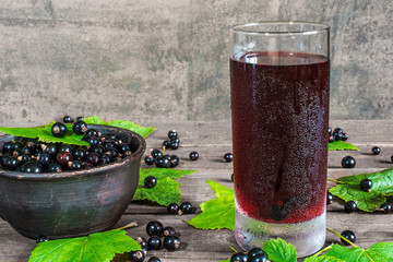 glass of cold black currant juice with fresh berries in a bowl
