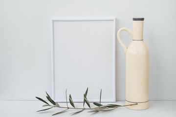Frame mockup on white background, ceramic bottle, olive tree branch, clean minimalist styled image for social image, marketing
