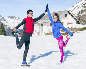 Couple of gymnasts doing exercises in the snow