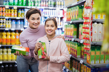 Female shopper with teenage daughter searching for beverages